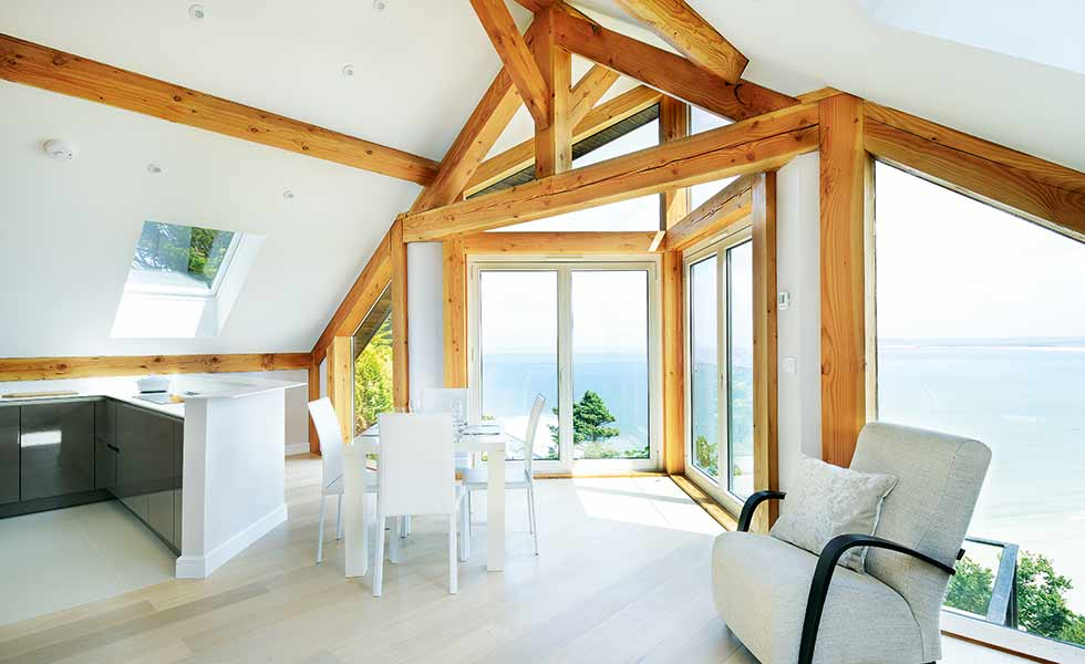 Full-height glazing and whitewashed timber flooring creates a light-filled interior in this Cornish chalet self build