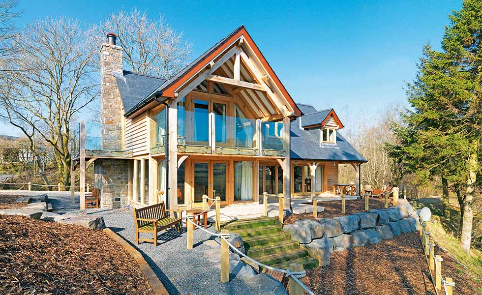 A balcony positioned in the gable end of this timber frame home in Powys acts a a focal point