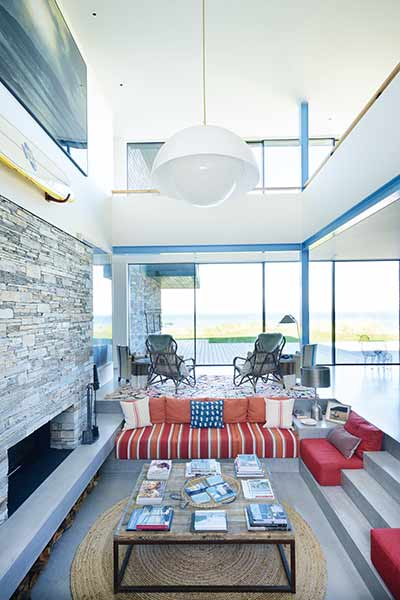 Sunken seating in front of a feature fireplace in a home on the Cornish coast
