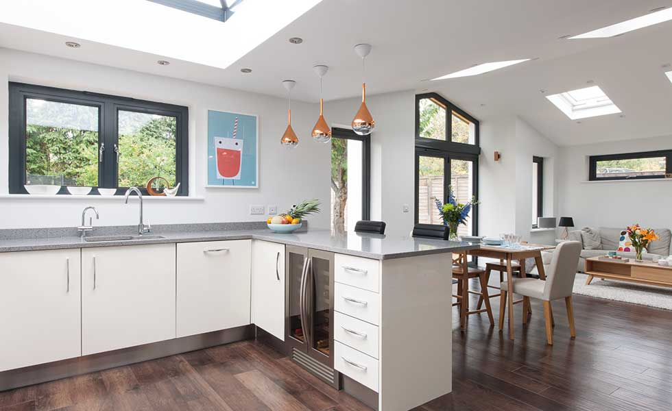 Contemporary white gloss open plan kitchen with breakfast bar and roof lantern