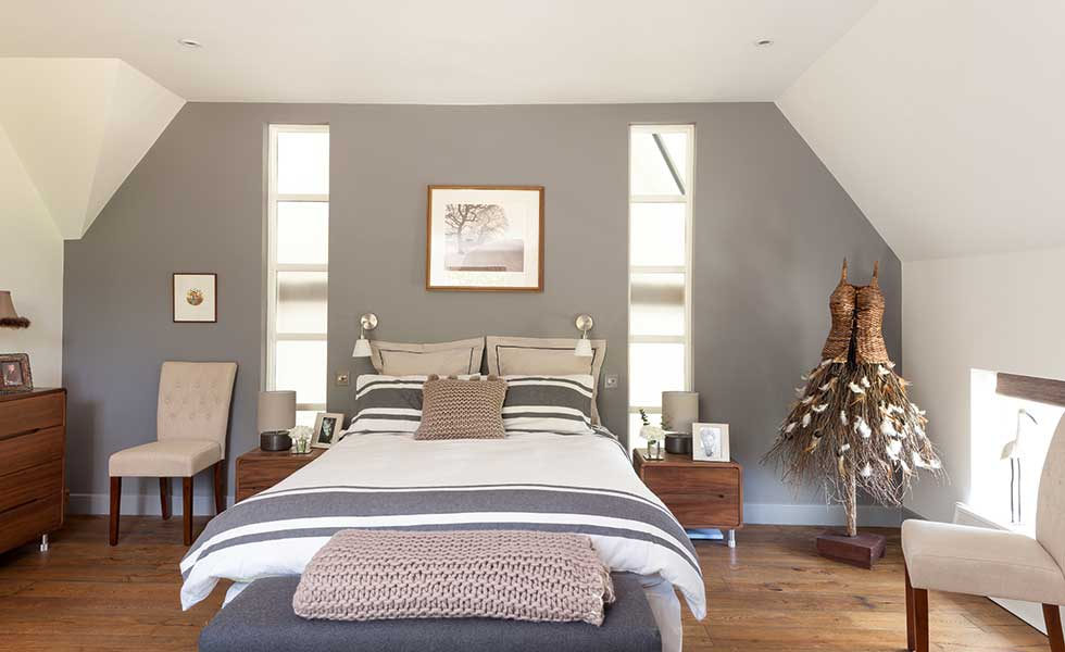 Thin picture windows either side of the bed in this master suite help bring in borrowed light from other spaces in the home, but offer privacy too
