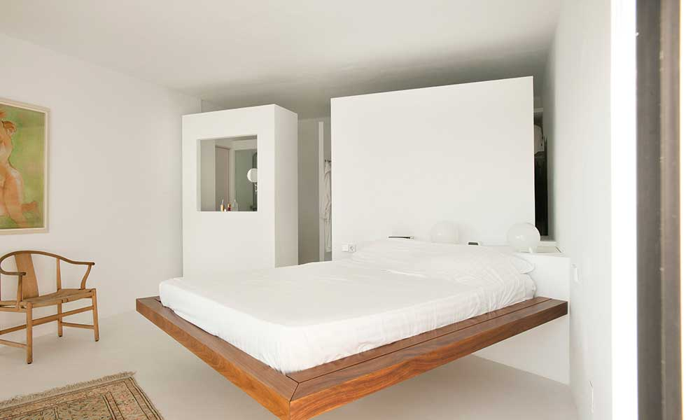 A cantilevered bed frame in this master suite adds visual interest