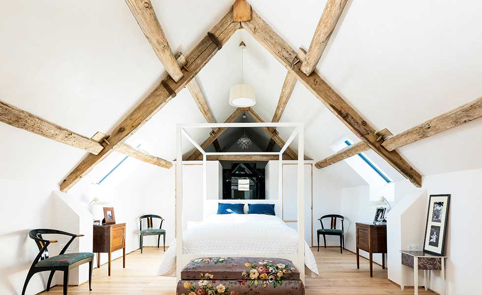 This master suite within the roof space of this barn conversion features vaulted ceilings for dramatic effect