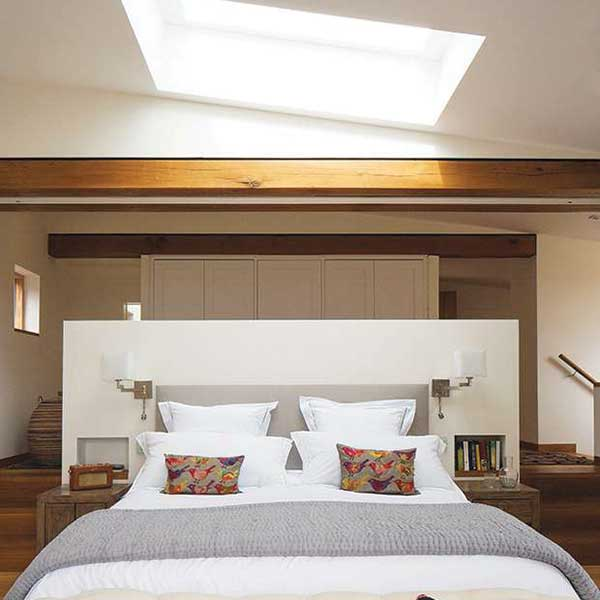 A roof light above the bed in this master suite casts views to the sky