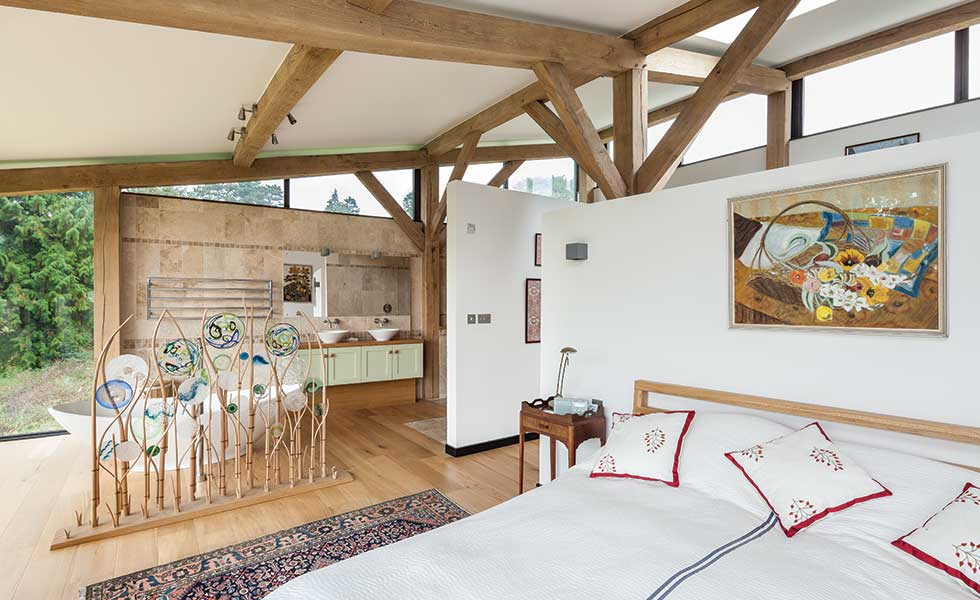 This master bedroom in Gloucestershire is open plan to the bathroom and evokes a hotel style