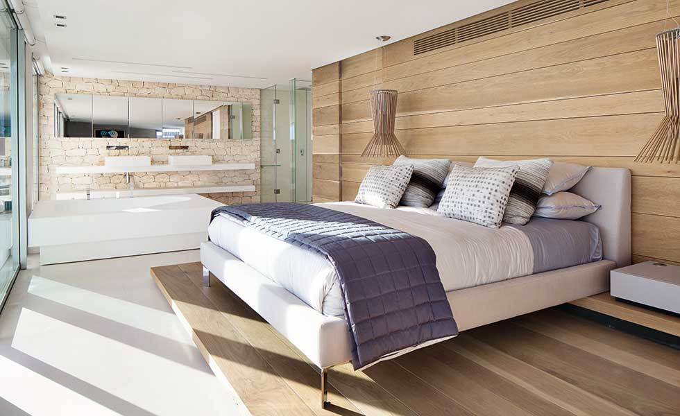 A bed sits on a platform of timber panels in this master suite