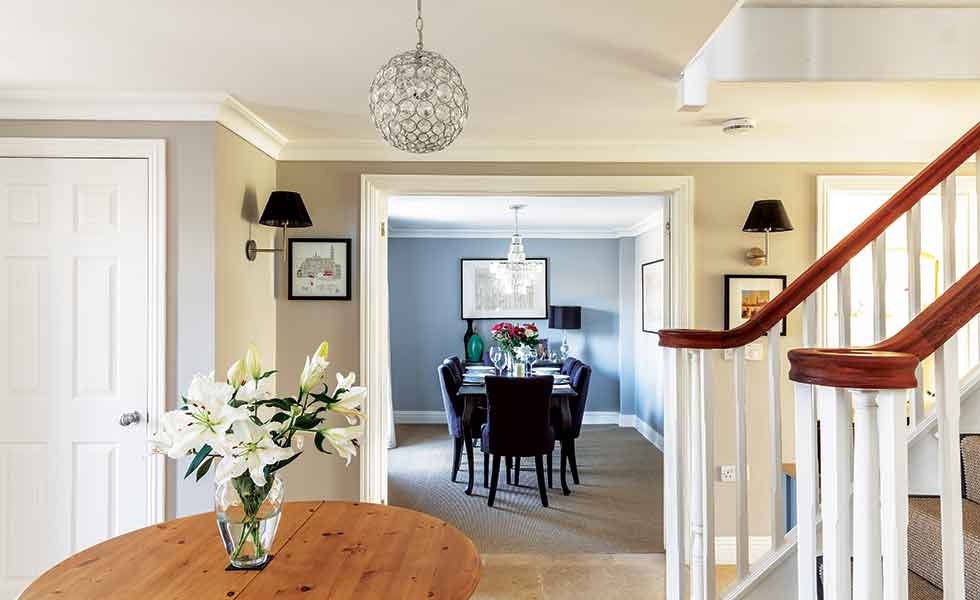 The grand hallway with central staircase and galleried landing opens to various reception rooms on the ground floor