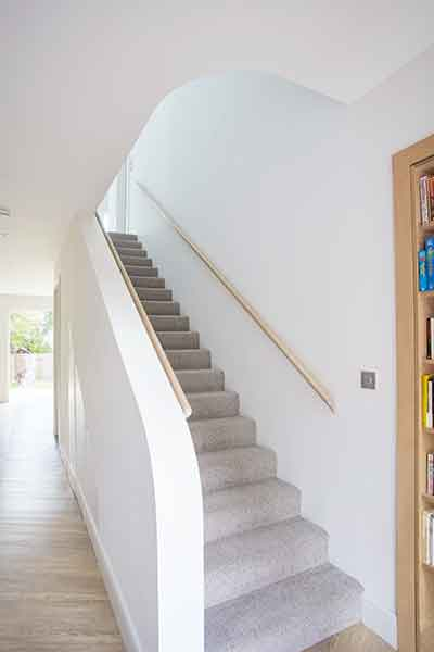 A timber staircase incorporates curves in this prefabricated home