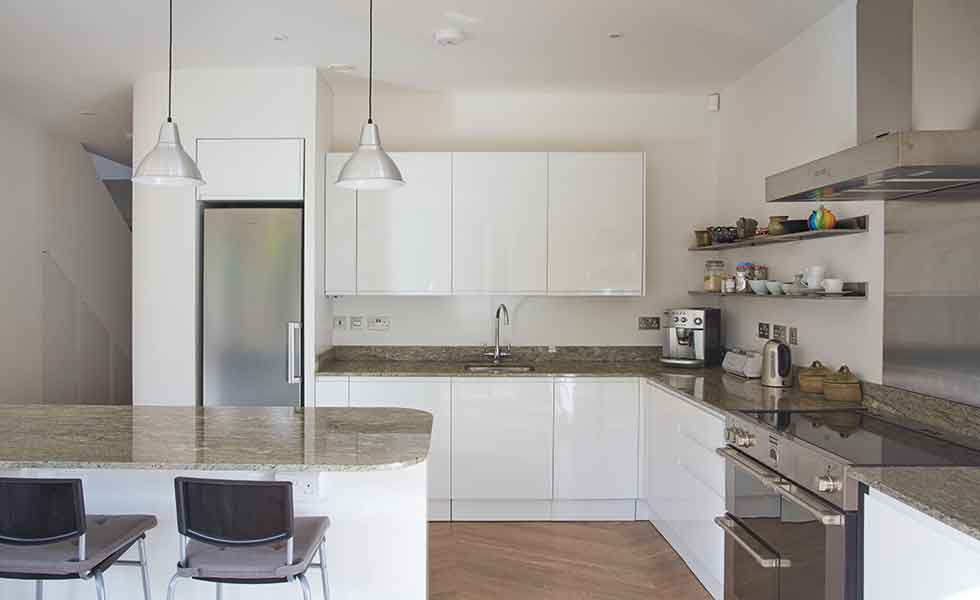 White gloss units and granite worktops feature in this prefabricated timber frame home