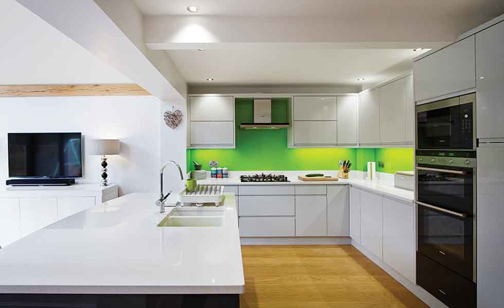 Green splash backs contrast against the white gloss kitchen units in this oak frame extension