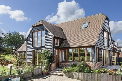 Traditional materials such as clay roof tiles and stained weatherboarding mean this new home sits comfortably into its surroundings