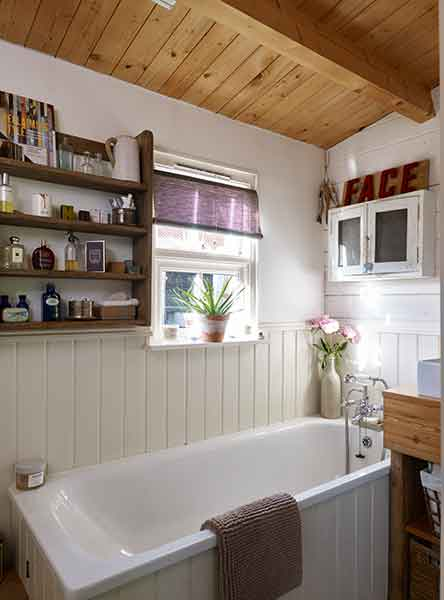 The bathroom in the log cabin features timber wall panels