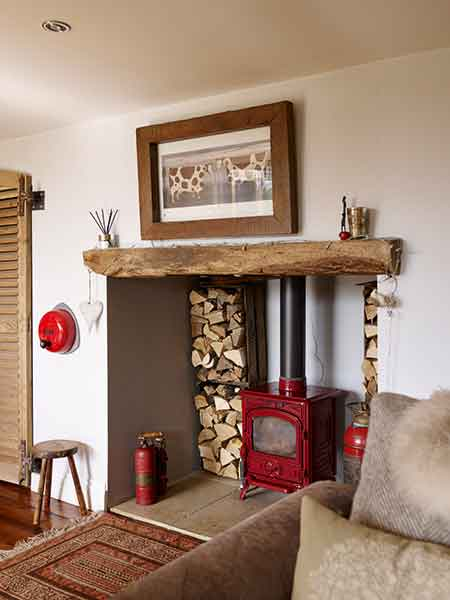 A woodburning stove offers warmth to the log cabin