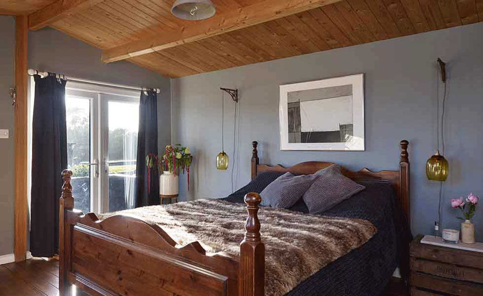The master bedroom in the log cabin has been designed with a rustic feel