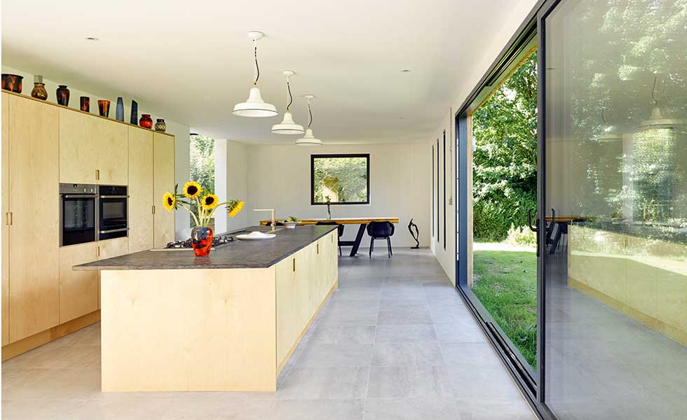 A modern kitchen design has been used in this extension project, with raw materials cladding the cupboards