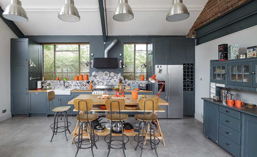 This industrial-style kitchen oozes modern charm in this characterful church conversion. Dark blue units carry through to the walls, while stainless steel appliances add a modern edge