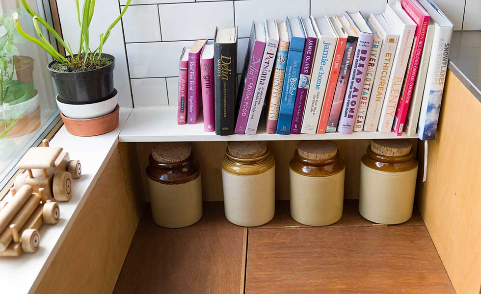 book shelf and concealed storage benches in kitchen window seating