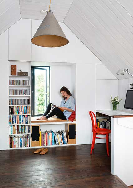 Clare Williamson sits in the window seat formed by built in storage in the loft room of a tiny efficient self build