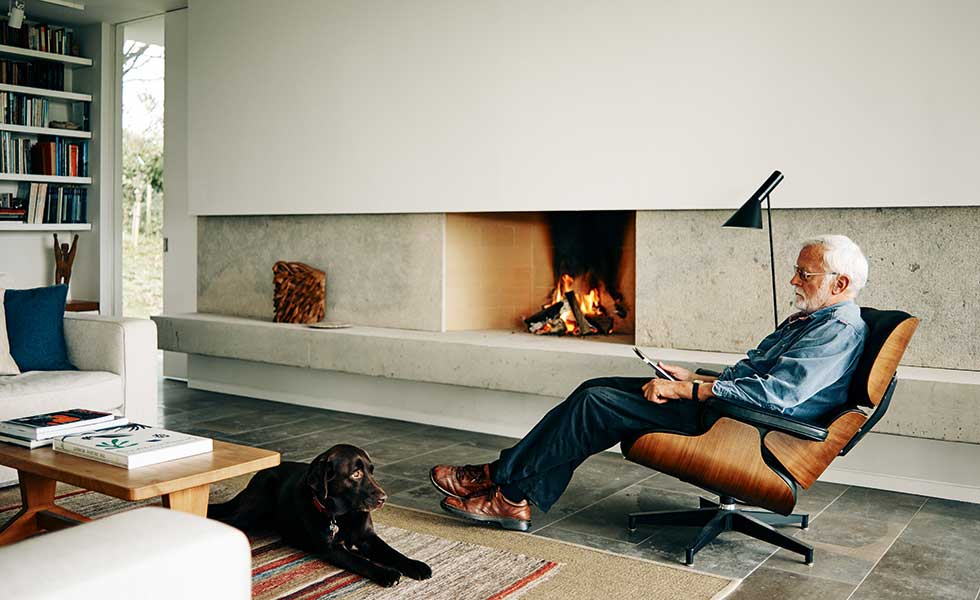 Labrador and man in Eames recliner in modern living room with open fire