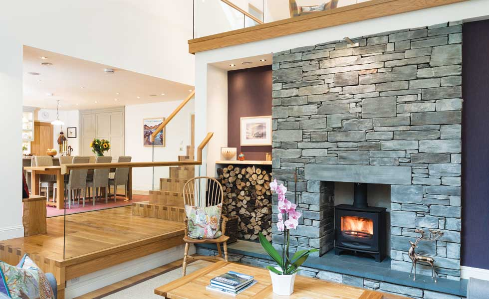 Split level living room with woodturning stove in slate chimney breast
