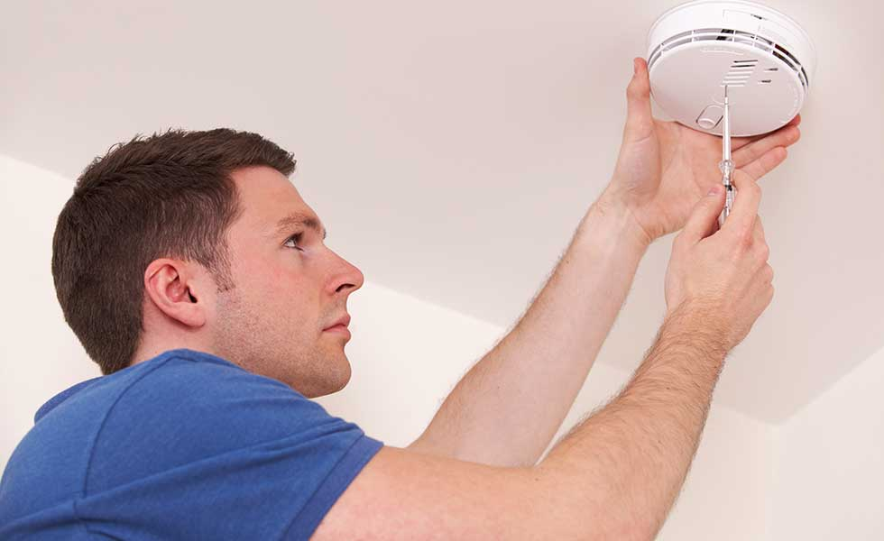 man fitting a safety alarm such as a smoke alarm