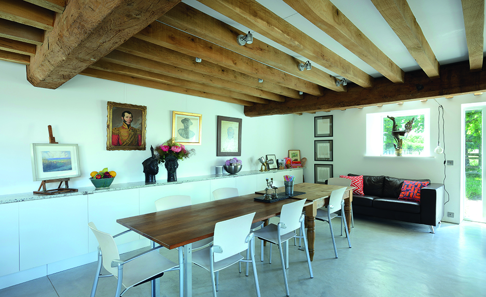Dining space in barn conversion with polished concrete floors and exposed beams