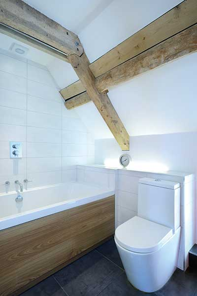 Contemporary bathroom with sloping ceiling and exposed beams