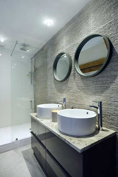 En suite shower room with twin basins and stone tiled walls