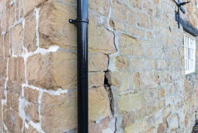 a crack in the external wall of the farmhouse wide enough to fit a hand in