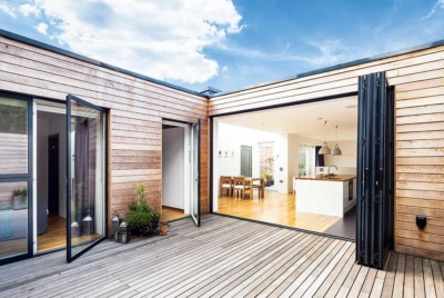 wood clad home opening onto internal courtyard with decking