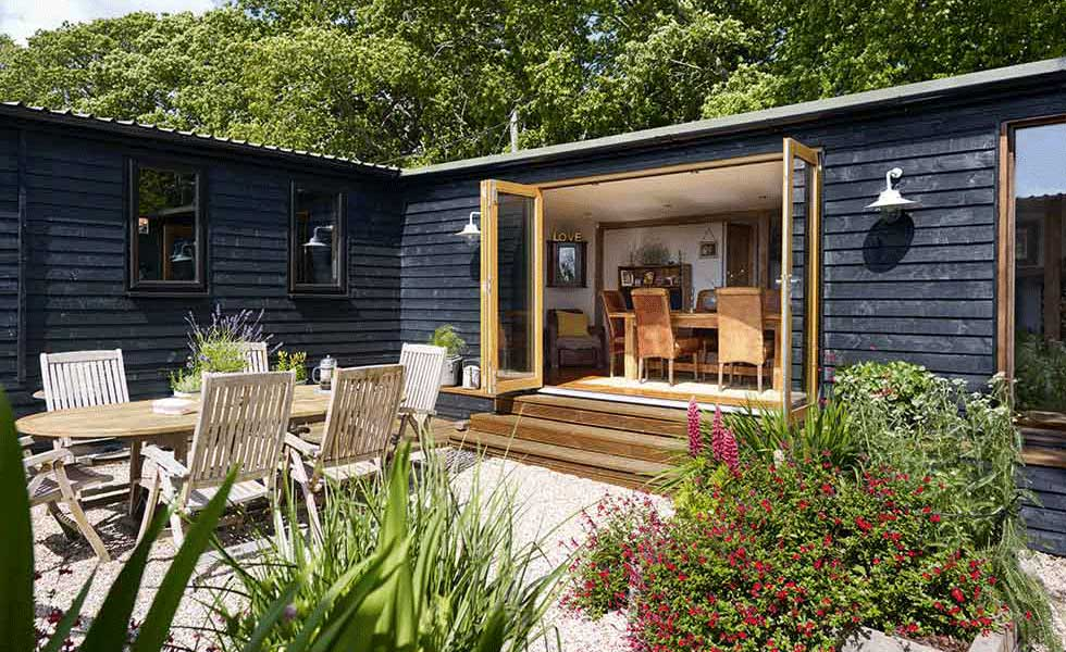 black stained log cabin onto courtyard dining area
