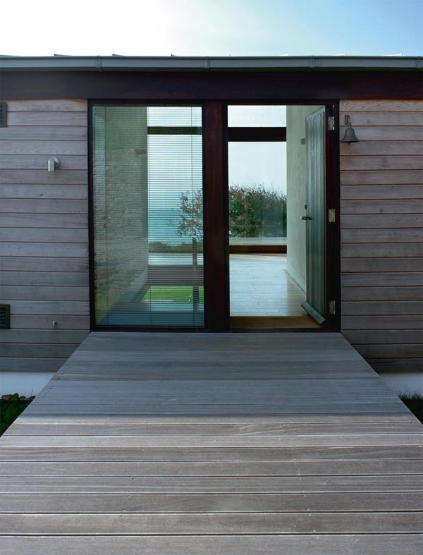 This unusual entrance features a walkway bridge leading to the front door