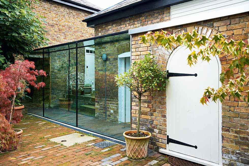 Using glass to create a link between two buildings is a great way to introduce light