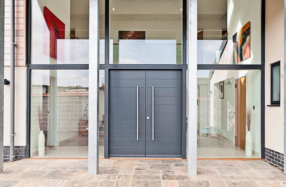 Full-height glazing and sidelights either side of the front door help to bring in light into the hallway
