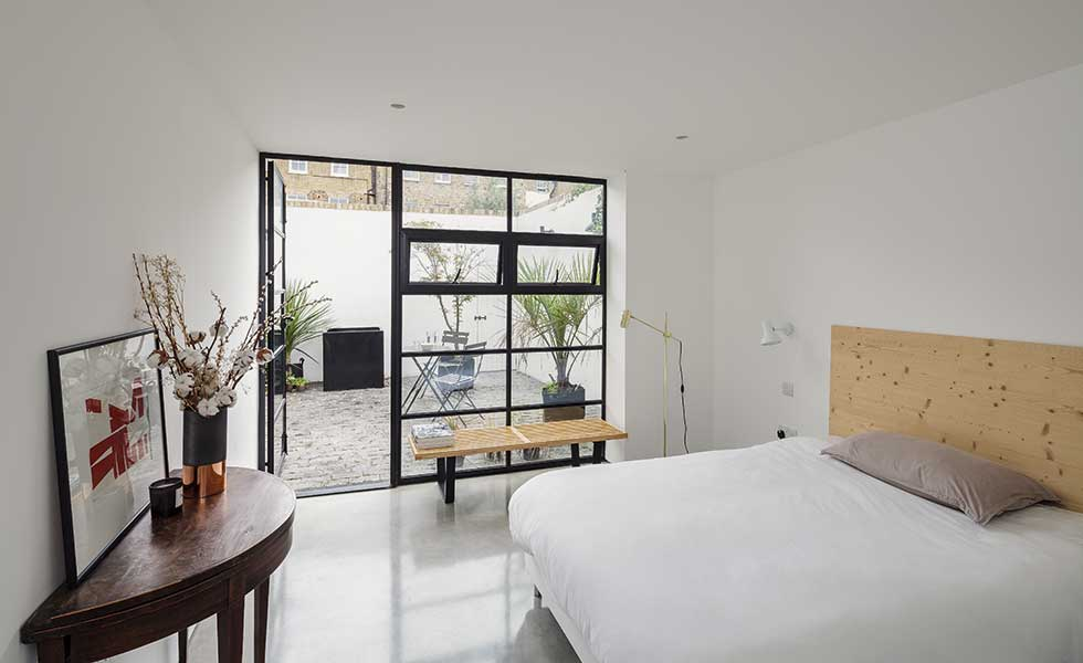 The bedroom on the ground floor of this conversion project in London opens out onto a courtyard