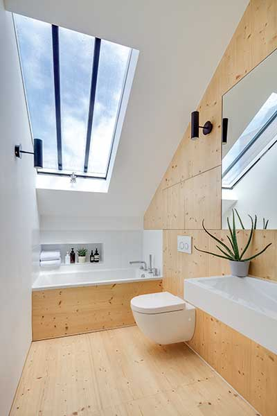 The en suite in this conversion project is flooded with natural light thanks to a large rooflight over the bath