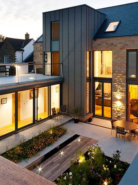 Working with the sloping nature of the site, this home's entrance is approached via a bridge, and also makes way for a sunken courtyard below.