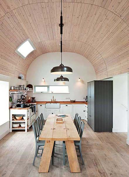A curved ceiling clad in timber creates an unusual focal point in this renovation project, leading the eye upwards.