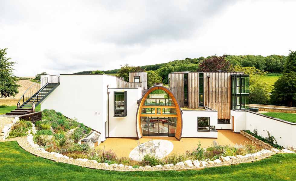 The unusual entrance to this home boasts an impressive double-height span shaped in the form of a barrel (the homeowners are big wine connoisseurs), with glazing offering through-views down the centre of the home