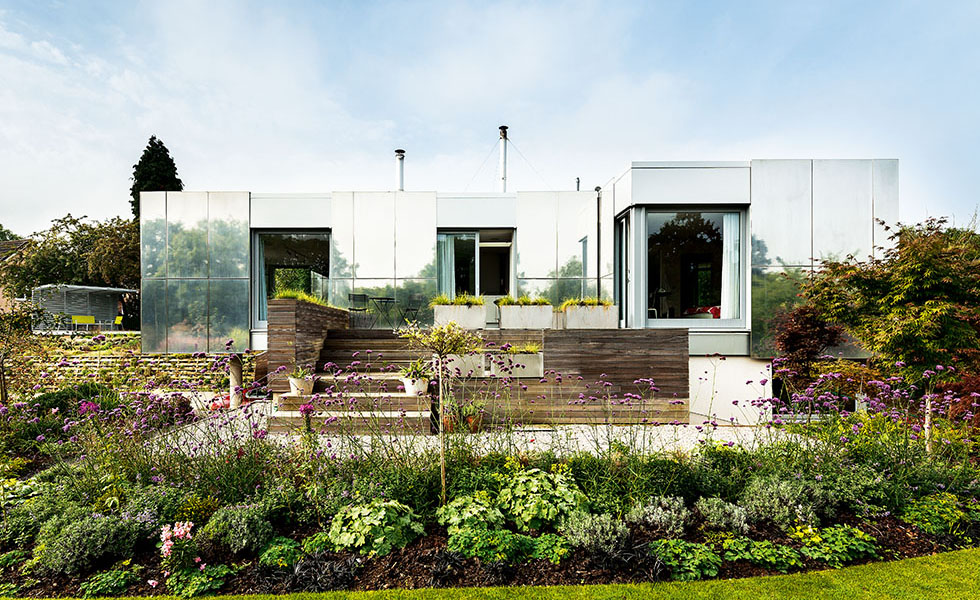 An unusual mirrored façade on this project helps to reflect the landscaping and embed the house within its surroundings