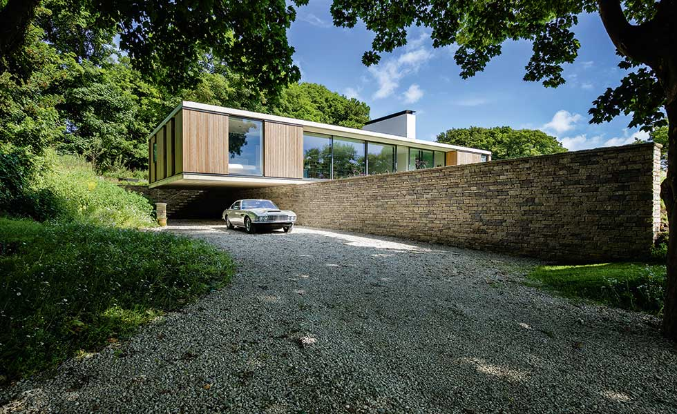 classic-car-outside-cantilevered-self-build-with-gravel-drive
