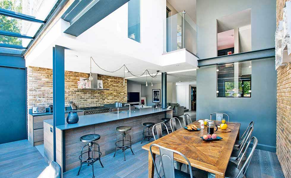 In this American loft-style self build in Surrey, the open plan kitchen/dining/living space is broken up into zones thanks to the jagged ceiling made up of varying levels. The kitchen sits under a lower ceiling while the dining space opposite boasts views up to the roof. Exposed steel beams and glazed mezzanines add to the jagged effect