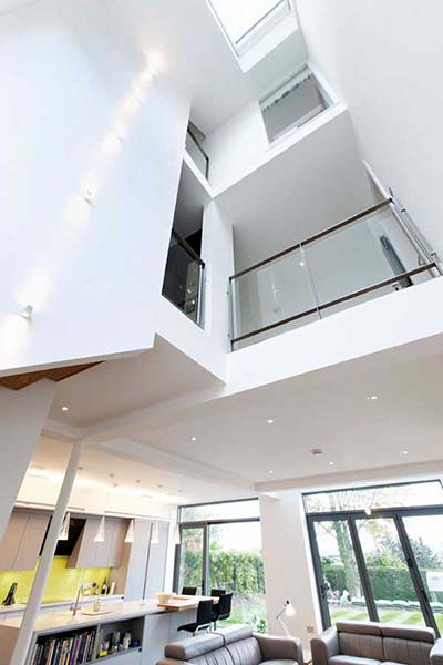 A dramatic triple-height void in this contemporary self build leads the eye upwards thanks to a rooflight positioned at the apex. Galleried sections with glazed balustrades at first and second floor level allow each part of the home to enjoy views up and down the void.
