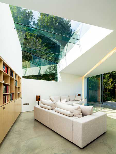 In this extension project, the tall ceiling has been punctured with structural frameless glazing which moves down the rear wall. Combined with the design of the glazing sitting above the ceiling height to one side of the room, the homeowners benefit from an open air feel.