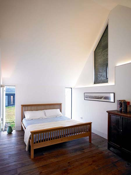The steeply sloping pitch of the ceiling in this bedroom creates an almost triangular shaped space