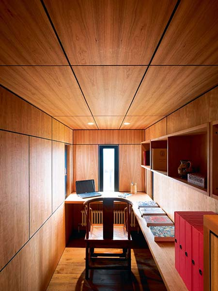 A low ceiling clad in timber to match the walls creates a cosy, enclosed space for a home office in this renovation project.