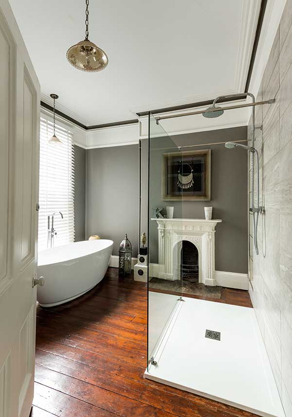 Luxury bathroom in Victorian house with original fireplace