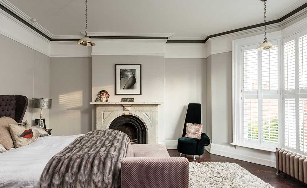 Master bedroom in Victorian house with original fireplace
