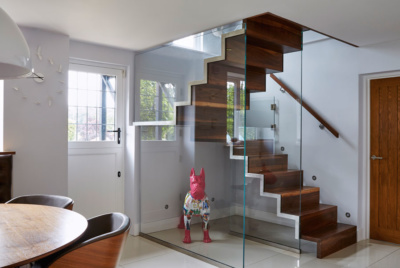 Two glass walls support this staircase design, separating it from the rest of the room, but still allowing light in
