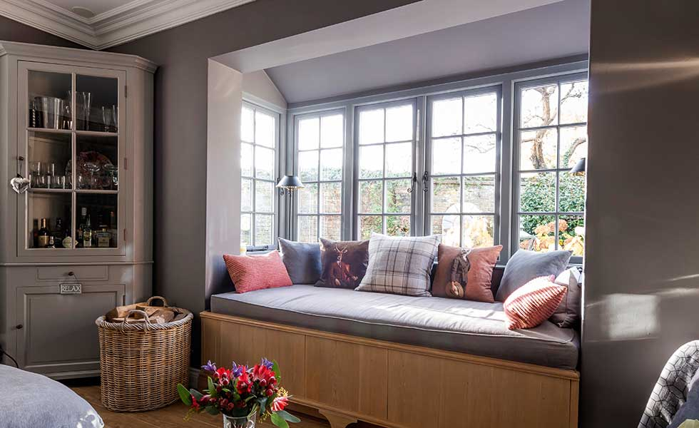 In this project, the deep bay window has been utilised to house a comfortable window seat which also offers additional seating in the living room